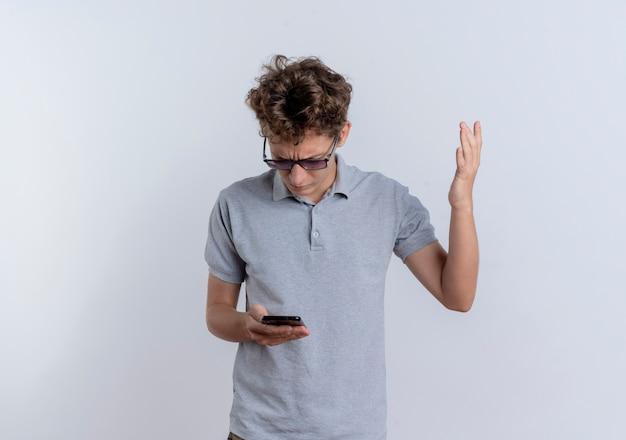 회색 폴로 셔츠에 젊은 남자가 자신의 스마트 폰 화면을보고 손을 들고 흰 벽 위에 서 혼란스러워