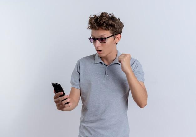 회색 폴로 셔츠에 젊은 남자가 흰 벽 위에 서 행복하고 흥분된 주먹을 떨리는 그의 스마트 폰의 화면을보고