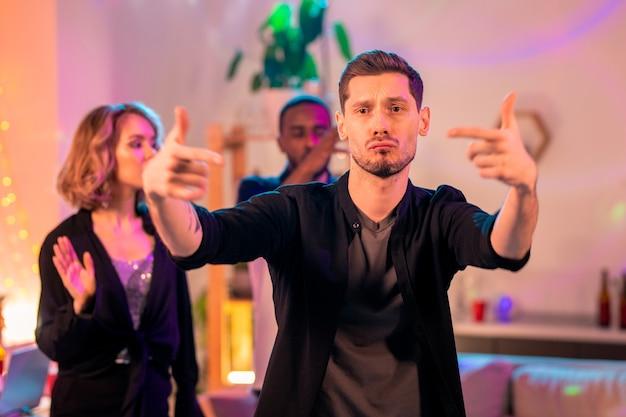 Молодой человек в серой футболке и черной рубашке танцует на домашней вечеринке на фоне восторженной блондинки и африканского парня