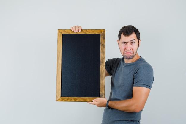 칠판을 들고 의심스러운 찾고 회색 티셔츠에 젊은 남자