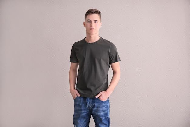 주머니에 손을 포즈 회색 티셔츠에 젊은 남자