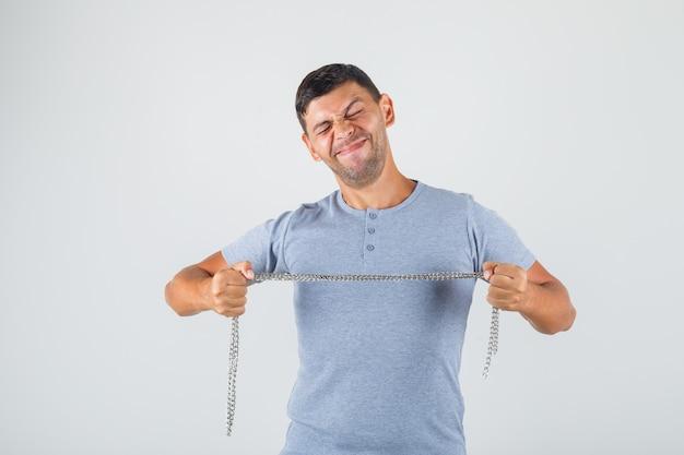Молодой человек в серой футболке тянет за цепь с закрытыми глазами и выглядит решительно