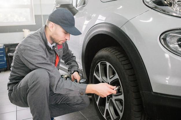 灰色の制服を着た若い男は、ホイールの前でチームの位置に座っています。彼はそれを見て、タイヤを修理します。