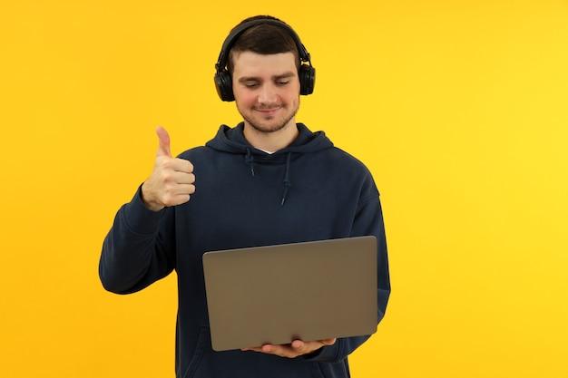 Молодой человек в наушниках держит ноутбук и показывает палец вверх на желтом фоне.