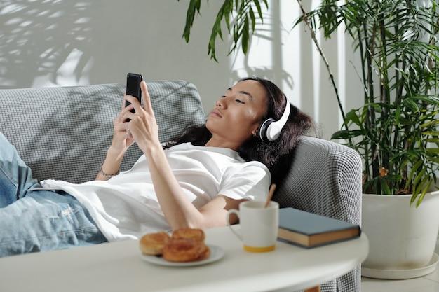 音楽を聴いたり、友達にテキストメッセージを送ったり、中毒性のあるゲームをしたりして、ソファに横になっているヘッドフォンの若い男...