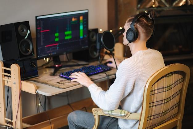 헤드폰에 젊은 남자가 pc와 두 전문가를 사용하여 집에서 팟 캐스트 오디오 녹음을 만든다