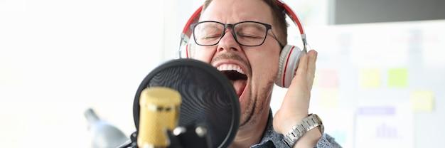 Молодой человек в наушниках поет в микрофон эмоциональное пение концепции
