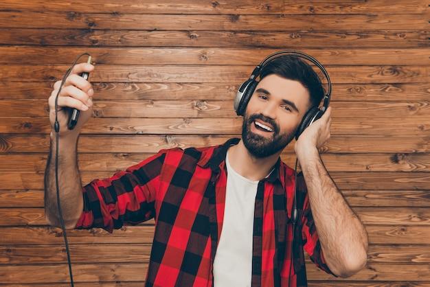 나무 벽에 노래하는 헤드폰에서 젊은 남자