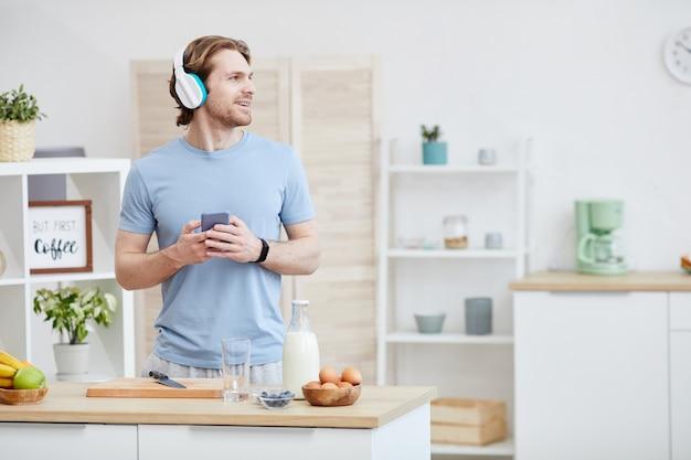 キッチンで朝食を調理しながら携帯電話で話しているヘッドフォンの若い男