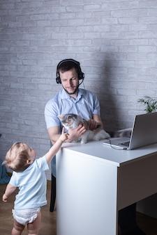 ヘッドフォンで若い男が自宅で仕事し、彼の赤ちゃんの息子と愛撫猫とベビーシッター