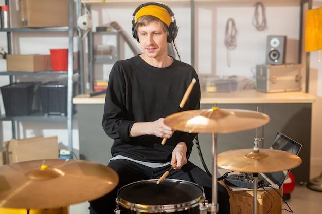헤드폰, 노란색 비니, 검은 셔츠에 젊은 남자