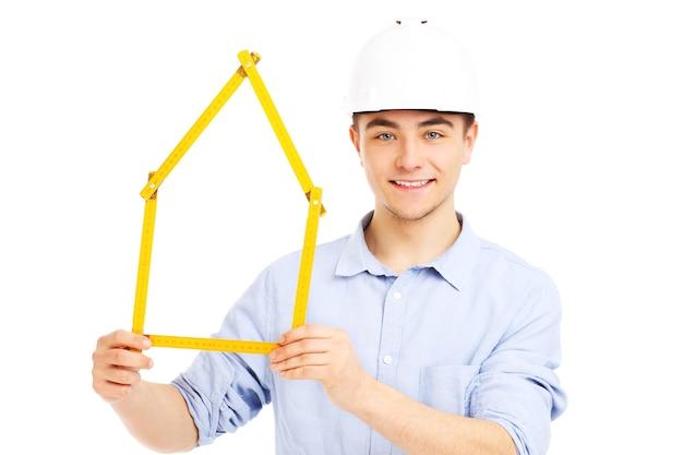 白い背景の上の家を保持しているヘルメットの若い男