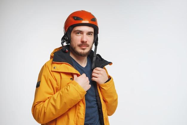헬멧을 쓴 젊은 남자가 흰색 배경에 격리된 스튜디오에서 포즈를 취하고 있습니다.