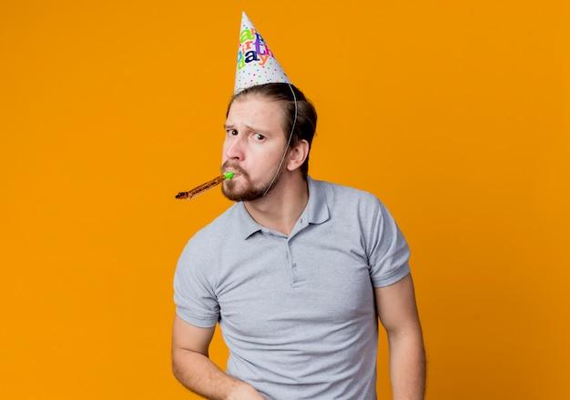 オレンジ色の壁の上に立っている笛の誕生日パーティーのコンセプトを吹くホリデーキャップの若い男