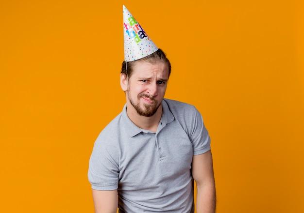 오렌지 벽 위에 서 불쾌한 생일 파티 개념을 찾고 휴가 모자에 젊은 남자