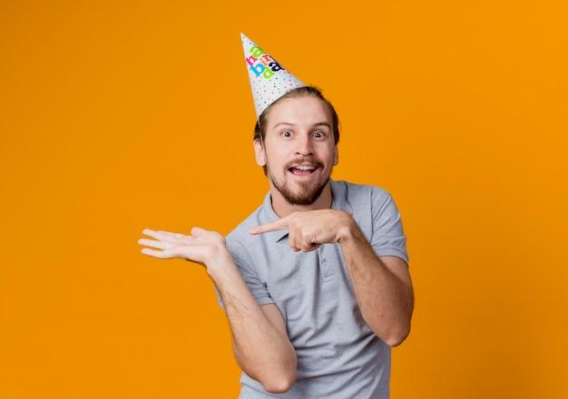 Молодой человек в праздничной кепке, представляя руку и указывая пальцем в сторону концепции вечеринки по случаю дня рождения, стоящей над оранжевой стеной
