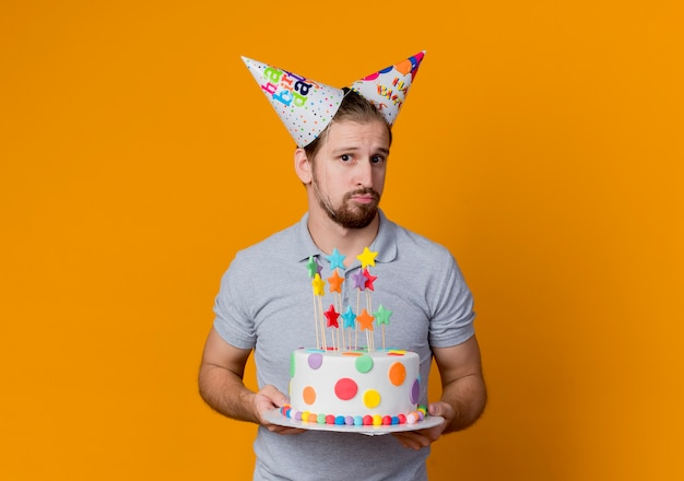 Молодой человек в праздничных кепках смущен, держа в руках праздничный торт на день рождения, стоя над оранжевой стеной