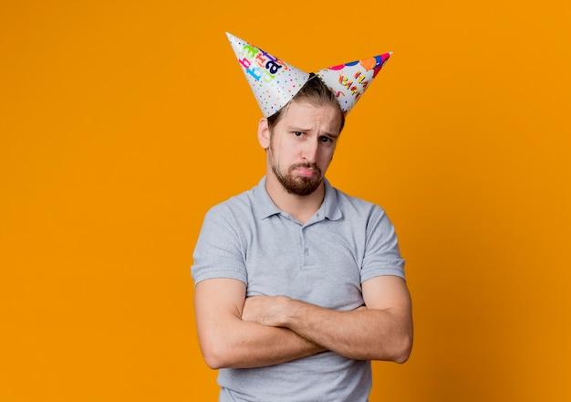 Молодой человек в праздничных шапках недоволен концепцией вечеринки по случаю дня рождения, стоящей над оранжевой стеной