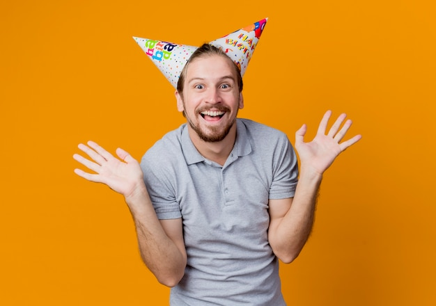 オレンジ色の壁の上に立って幸せで興奮した誕生日パーティーのコンセプトに笑みを浮かべて休日の帽子の若い男