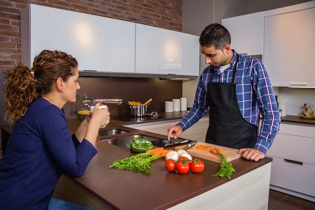 家庭の台所で食事を準備し、電子タブレットでレシピを探している若い男。現代の家族のライフスタイルの概念。
