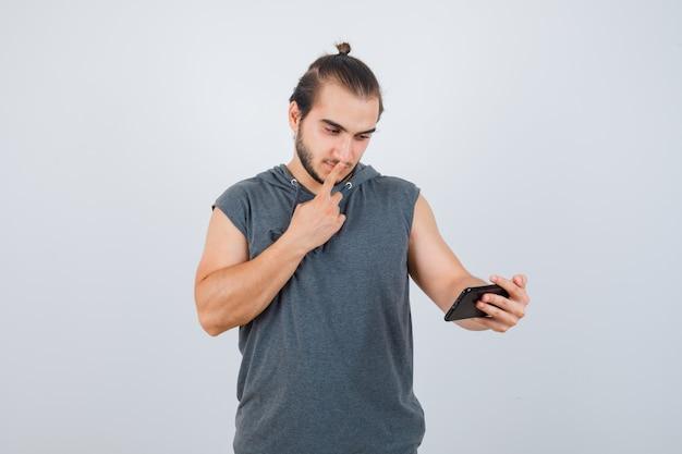 口に指を持って、電話を見て、物欲しそうな、正面図を見て、フード付きのtシャツを着た若い男。