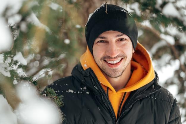 눈 덮인 공원에 서서 웃고 있는 후드티와 따뜻한 재킷을 입은 청년