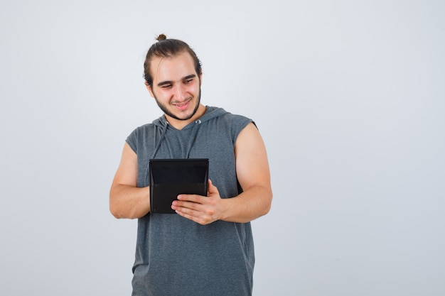 電卓を頼りに、思慮深く、正面図を探しているパーカーの若い男。
