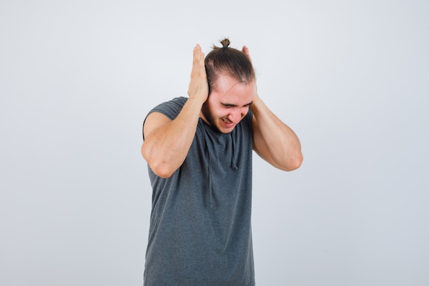 手のひらで耳を覆い、不満を探しているパーカーの若い男、正面図。