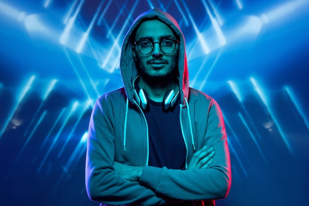 Молодой человек в толстовке с капюшоном, очках и футболке, скрестив руки на груди, стоя в синих огнях
