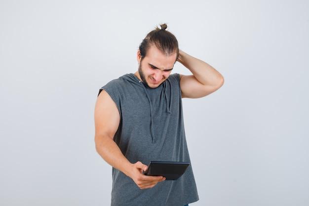 Молодой человек в толстовке с капюшоном, держащий руку за головой, глядя на калькулятор и довольный, вид спереди.