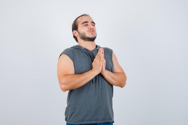 Молодой человек в толстовке с капюшоном показывает жест намасте и выглядит довольным, вид спереди.