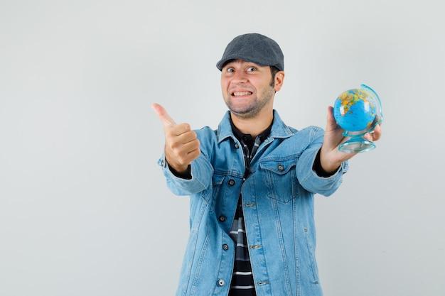 재킷에 젊은 남자, 엄지 손가락을 보여주는 동안 지구본을 들고 모자