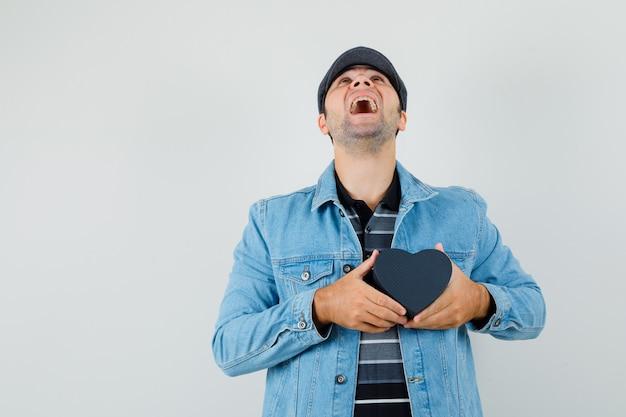 ジャケットを着た若い男、見上げて陽気に見ながらハート型の箱を持った帽子