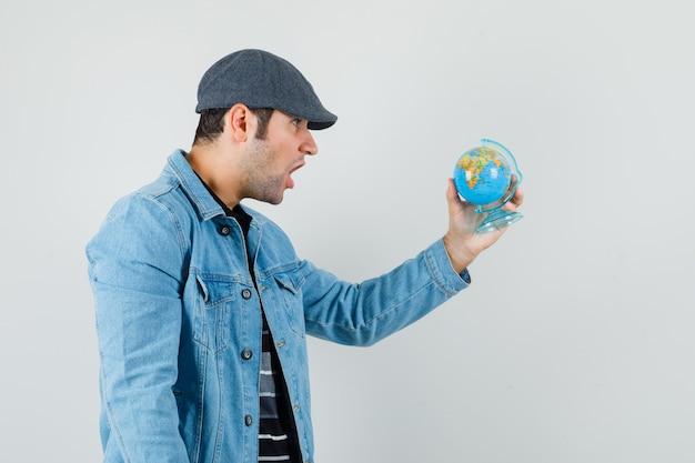 재킷에 젊은 남자, 모자는 지구본을보고 놀랐습니다.