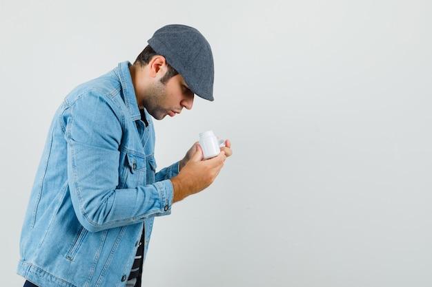ジャケットを着た若い男、薬瓶の中を見て、テキストのための気配りのあるスペースを探しているキャップ