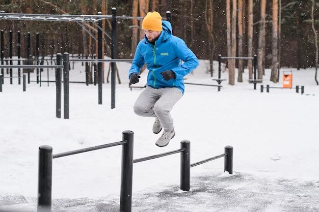 冬の屋外でトレーニングしながら、さまざまな高さの水平バーをジャンプするジャケットの若い男