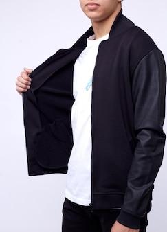 ジーンズ、白地に黒のボンバージャケットの若い男