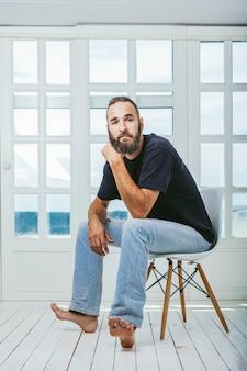 Молодой человек в джинсах с бородой хипстер сидит на стуле на заднем плане
