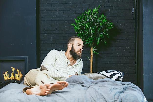 寝室のベッドに座っているヒップスターのひげを生やしたジーンズの若い男