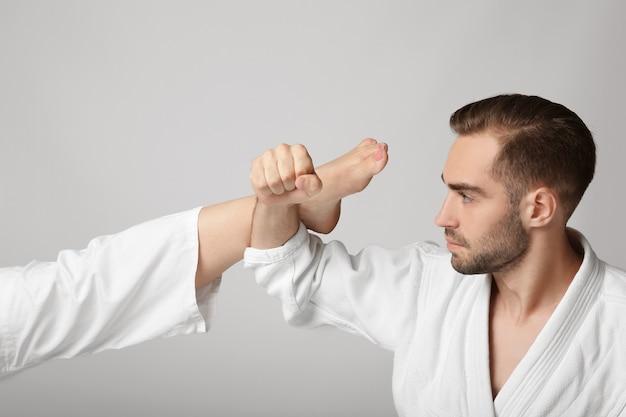 Молодой человек в каратэги блокирует удар на светлой поверхности