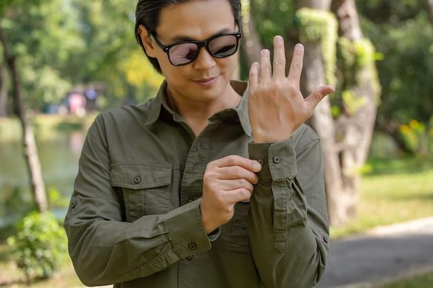 Молодой человек в рубашке с длинным зеленым рукавом стоит в парке