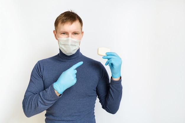 Молодой человек в медицинской маске на лице и синих медицинских резиновых перчатках держит кусок мыла в одной руке