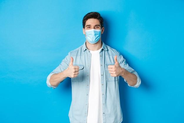 Молодой человек в медицинской маске показывает палец вверх в знак одобрения, нравится и соглашается, стоя у синей стены
