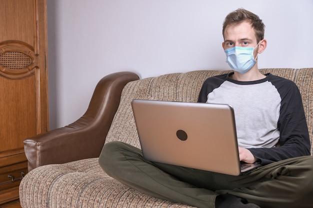 Молодой человек в медицинской маске, работающих на дому в комнате на диване, используя ноутбук. карантин, самоизоляция, защита от коронавирусов. отпуск с работы.
