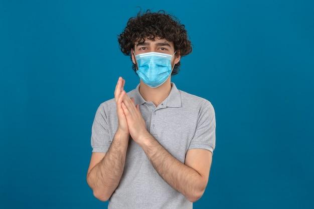 孤立した青い背景に手をこすりながらカメラを見て医療用防護マスクの若い男