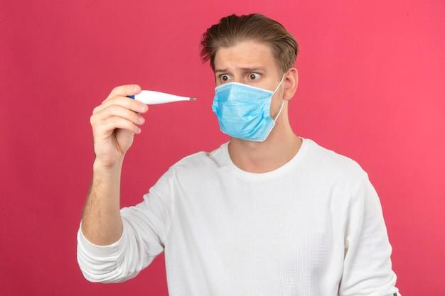 Молодой человек в медицинской защитной маске, глядя на цифровой термометр в панике, потрясен и удивлен на изолированном розовом фоне