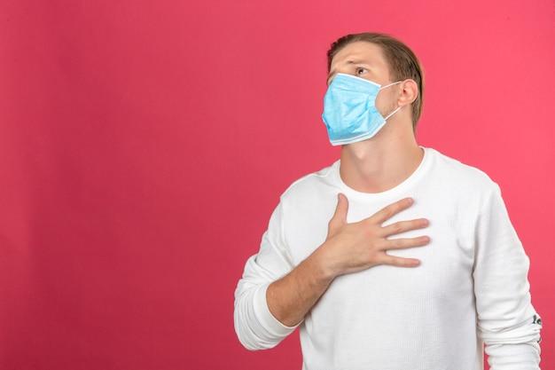 コピースペースと分離のピンクの背景に彼の胸に触れる病気とおびえた医療防護マスクの若い男