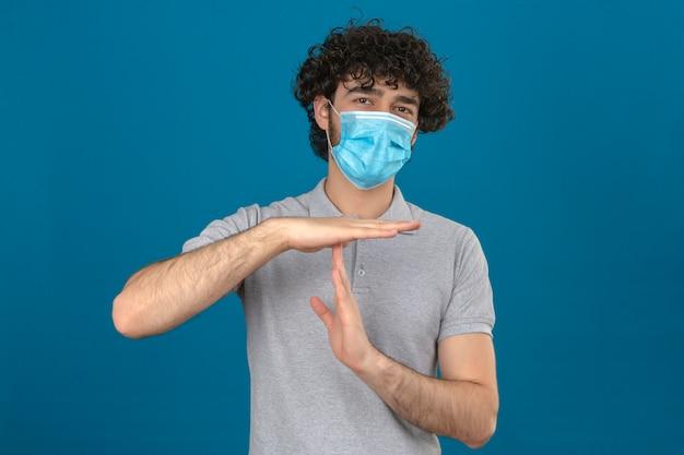 孤立した青い背景の上の手で病気と疲れを作るタイムアウトジェスチャーを探して医療用防護マスクの若い男
