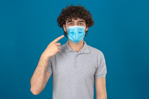 孤立した青い背景に笑顔でカメラを見て彼のマスクを指している医療用防護マスクの若い男
