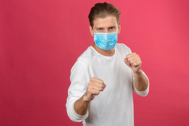 격리 된 분홍색 배경 위에 서 싸우는 의료 보호 마스크 펀치 주먹에 젊은 남자
